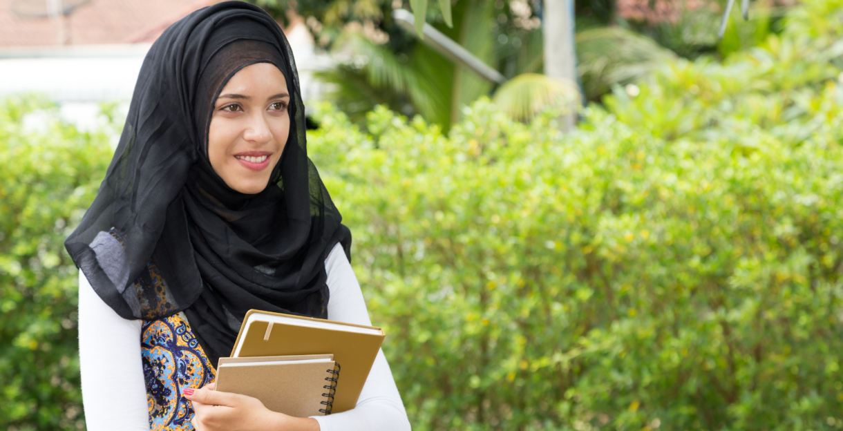 student holding books in kuwait